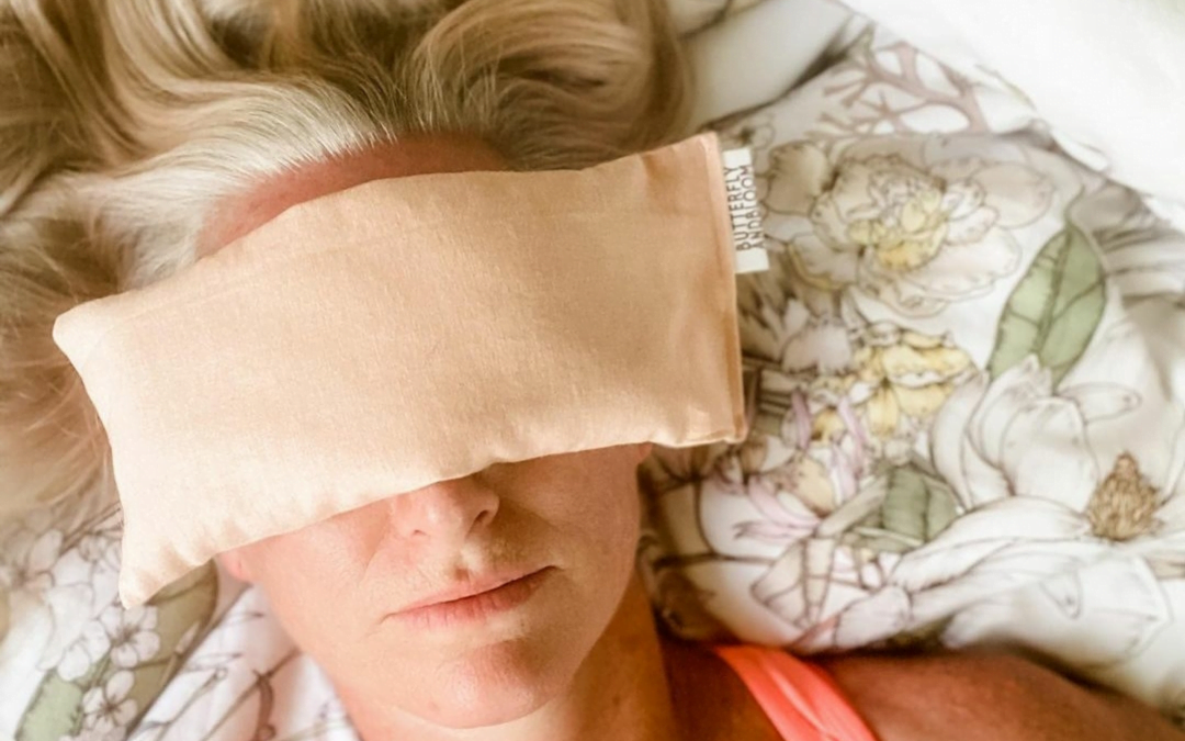 Woman lying down with pink eye pillow