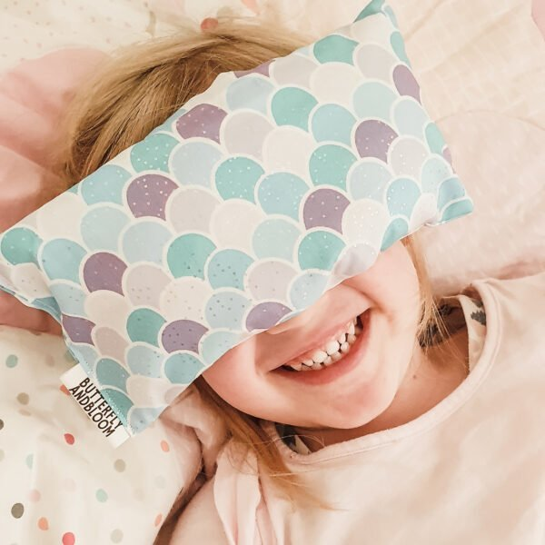Image of a smiling young girl with a mermaid scale eye pillow over her eyes