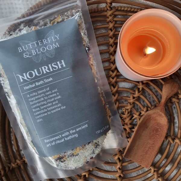 Nourish Herbal Bath and Foot Soak in a clear bag with green sticker with candle lit