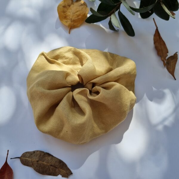 Handmade hair scrunchie with naturally dyed hemp fabric in a mustard colour
